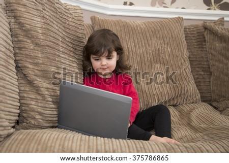Girls looking at laptop screen on sofa - stock photo