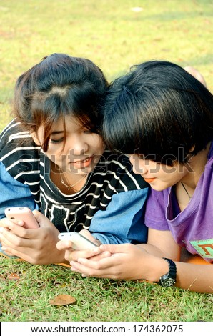 Girls looking at the mobile phone using some social media. - stock photo