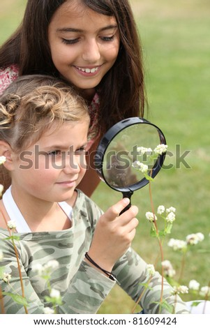 Girls looking through magnifying glass - stock photo
