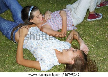Girls lying down in the garden. - stock photo