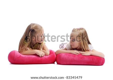 girls lying on the floor looking at each other - stock photo