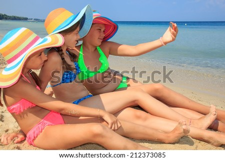 Girls making self portriat on the beach - stock photo