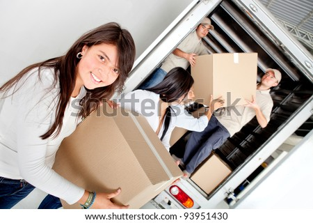 Girls moving house and unloading boxes from a truck - stock photo