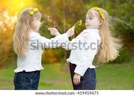 girls of the twin smell yellow dandelions in park in the spring - stock photo