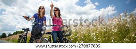 Girls on a bicycle trip in the country - stock photo