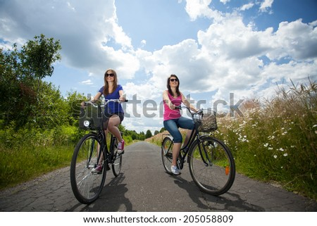Girls on a trip riding bicycles, horizontal - stock photo