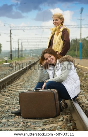 Girls on  railway sitting with her suitcase - stock photo