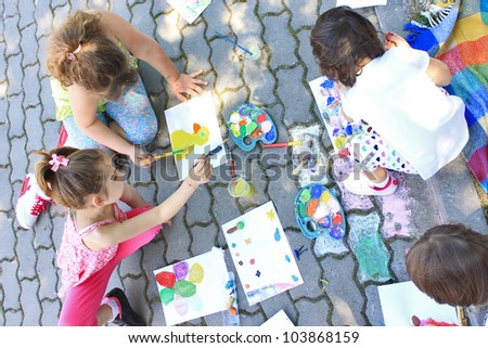 Girls painting outside - stock photo