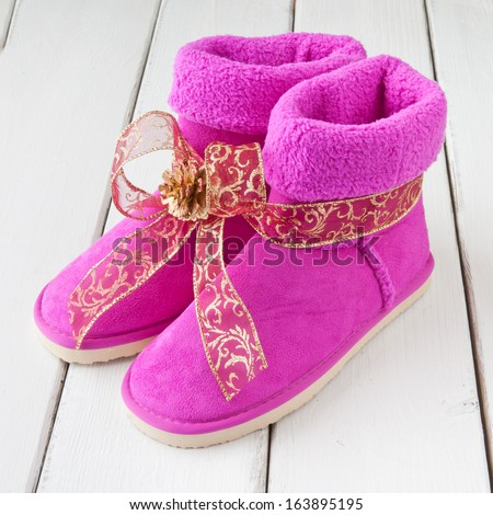 Girls pink winter boots as holiday gift with warm wishes - stock photo