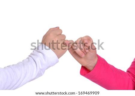 girls pinkie swear isolated on white background - stock photo