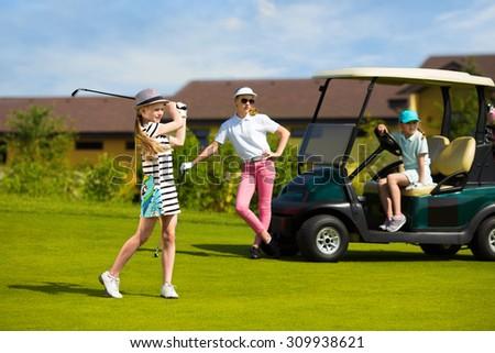 Girls playing golf at golf range at summer day - stock photo