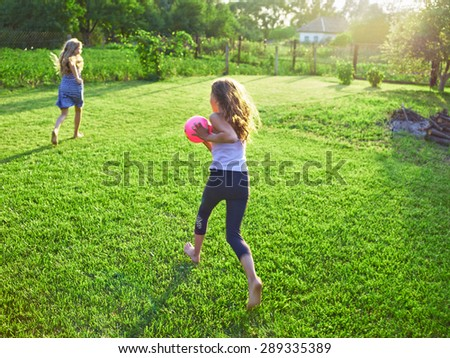 Girls playing with a ball in the rural backyard - stock photo