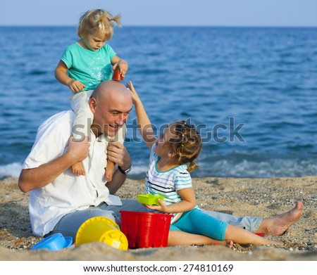 Girls playing with   father near sea. - stock photo
