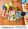 Girls playing with puzzle sitting on the floor in bedroom and looking up - stock photo