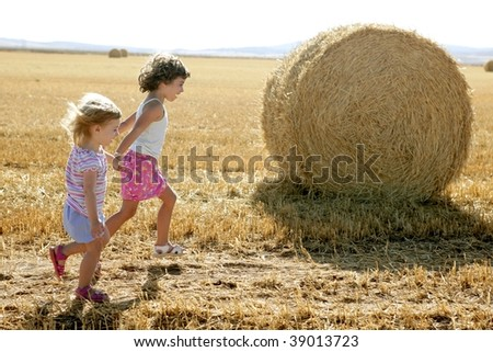 Girls playing with the round wheat dried bales outdoor summer - stock photo
