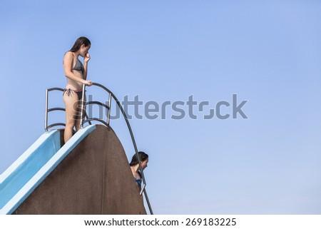 Girls Pool Slide Steps Playtime Girls teen on pool slide steps summer playtime fun. - stock photo