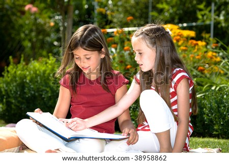 girls reading a book in the garden