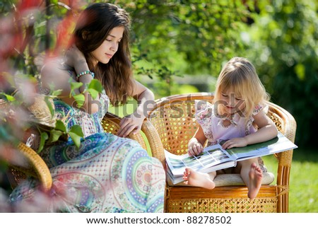 Girls reading book sitting in wicker chairs outdoor in summer day