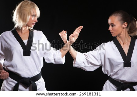Girls ready to fight,  because they taekwondo masters. Two wemen stay in positions on black background - stock photo