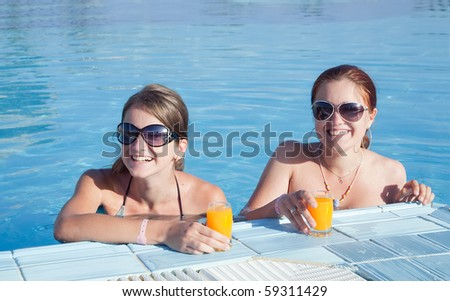 Girls relaxing in tropical pool with orange juice  at resort hotel - stock photo