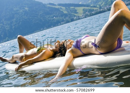 Girls relaxing on surfboard in Zell am See, Austria - stock photo