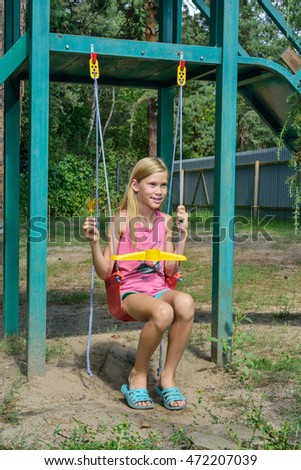 Girls ride on the swing and playing in the summer park