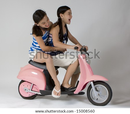 Girls riding a child scooter - stock photo