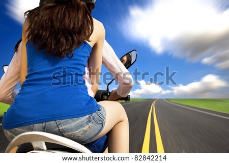 girls riding a motorcycle with high speed on a country road - stock photo