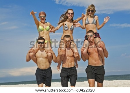 Girls riding on guys at  beach vacation - stock photo