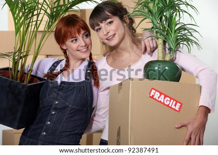 Girls roommates moving into their new apartment - stock photo