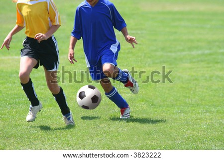 Girls running after the ball in a soccer match - stock photo