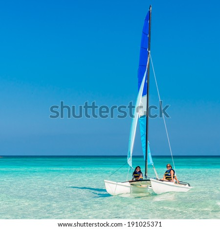 Girls sailing on a colorful catamaran at Varadero beach in Cuba - stock photo