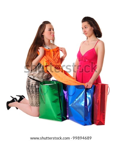 Girls shopping - one girl boasting before another of her newly bought fashionable dress - stock photo