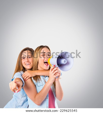 Girls shoutimg with megaphone over grey background - stock photo