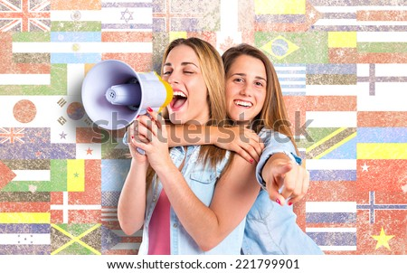 Girls shouting with megaphone over flags background - stock photo