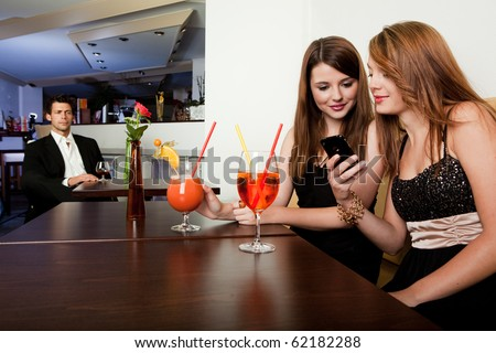 Girls showing cool stuff on a mobile phone to her friend - stock photo