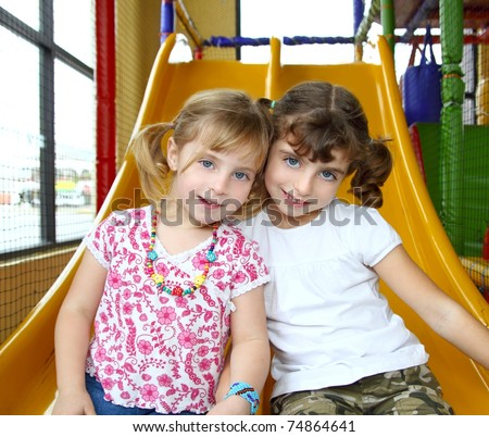girls sister friends on playground yellow play slide smiling portrait - stock photo