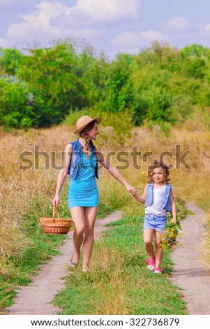 Girls sister in a field with a basket and flowers