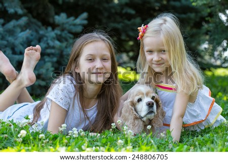 girls sisters  with dog looking at the camera  - stock photo