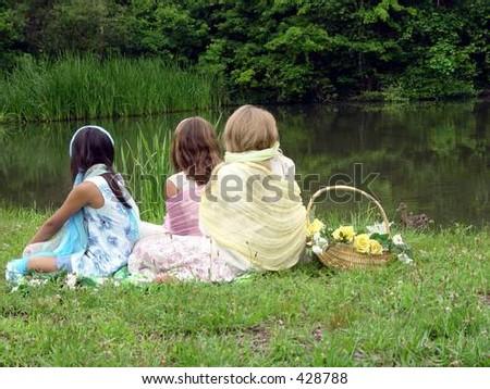 Girls sitting by lake - stock photo