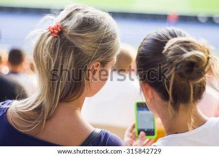 Girls sitting on a football and looking at the phone
