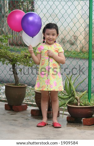 Girls smiling & holding colorful balloons - stock photo