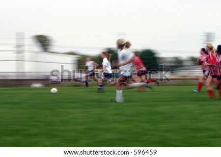 Girls soccer game with a long shutter to show motion of the game. - stock photo