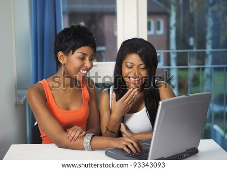 Girls socializing or chatting on internet laughing and having fun