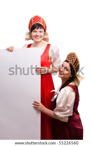 Girls standing in Russian traditional costume is smiling holding white blank card against isolated white background. Women is wearing sarafan and kokoshnik and is holding a blank white sign . - stock photo