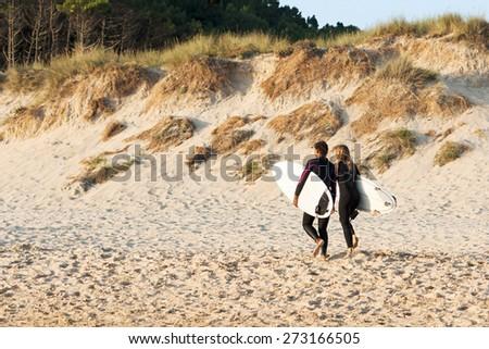 girls surfers  on seashore at sunset in Doninhos beach Galicia - stock photo