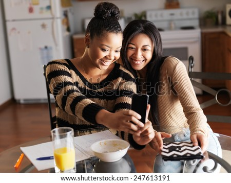 girls taking selfies with smartphone during breakfast - stock photo