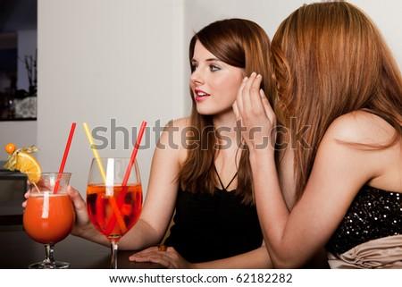 Girls talking gossips at the bar/restaurant/nightclub - stock photo