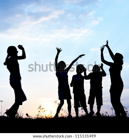 Girls teenagers and little boys dancing on field - stock photo