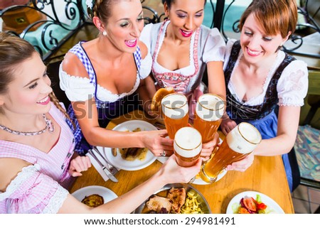 Girls toasting with wheat beer in Bavarian pub in front of pretzel - stock photo